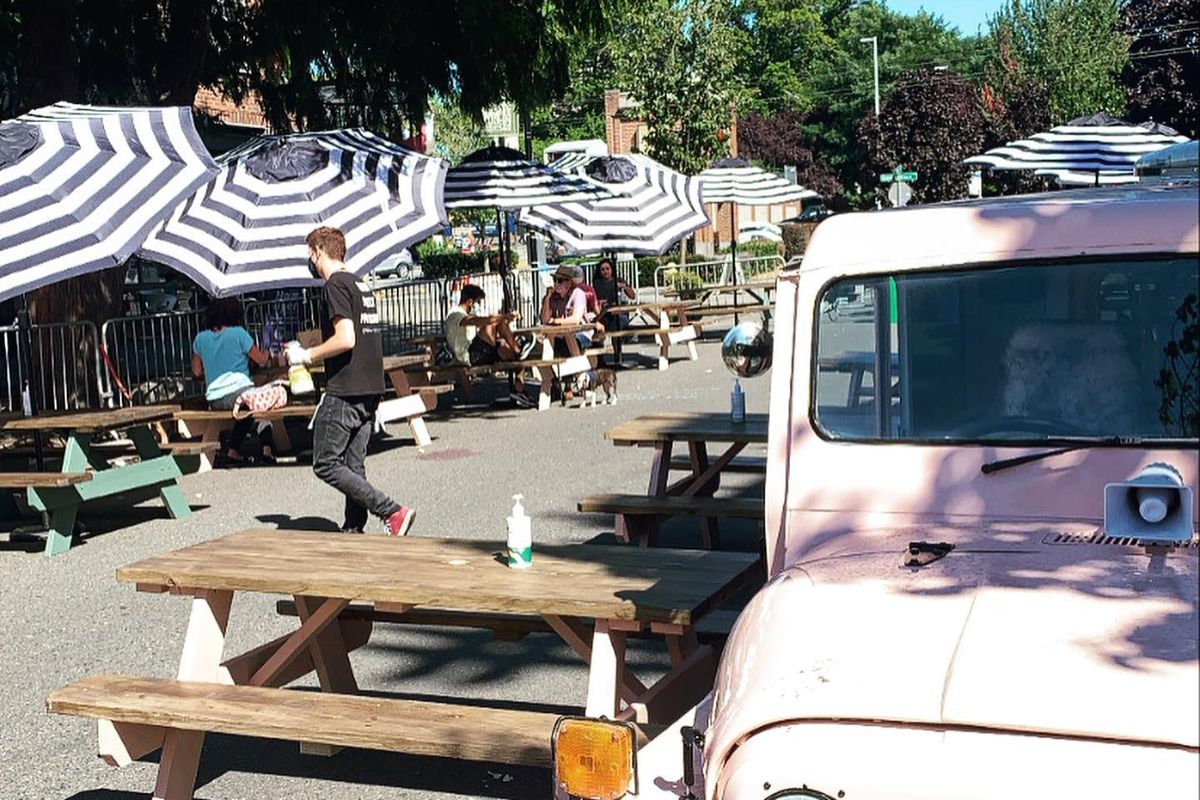 Tables are lined up on W Crockett Street in Queen Anne, with striped umbrellas and a masked server bringing food to customers. In the foreground is a pink jeep.