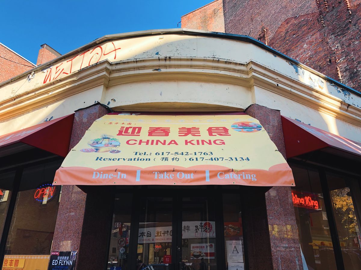 The facade of China King restaurants in Boston's Chinatown, which is made of brick and glass and adorned with a yellow and red awning.