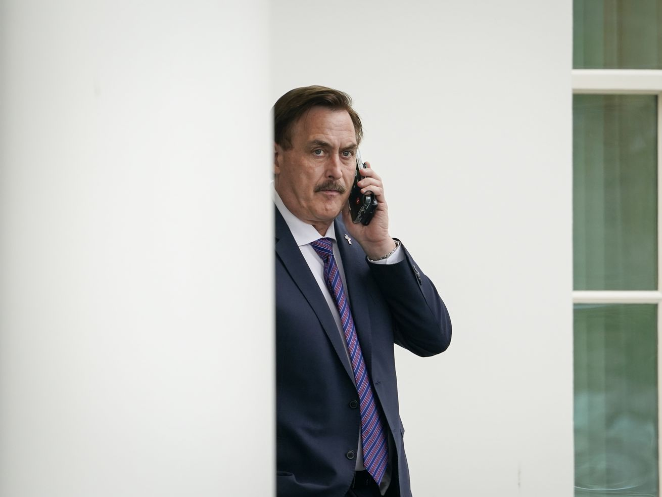 Mike Lindell on the phone peeking out from behind a pillar.