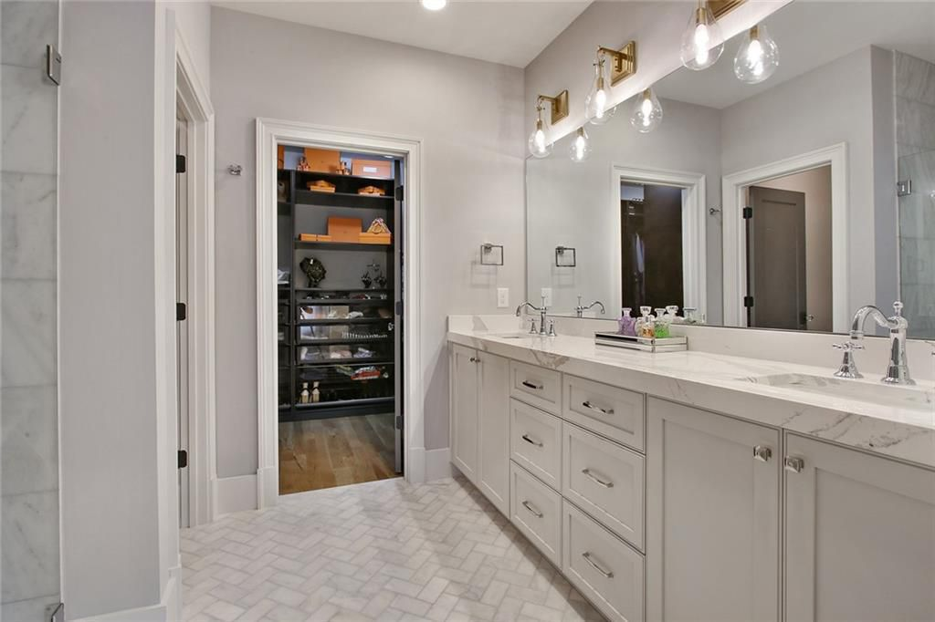 A master bathroom with two sinks and a lot of marble on the floors and walls.
