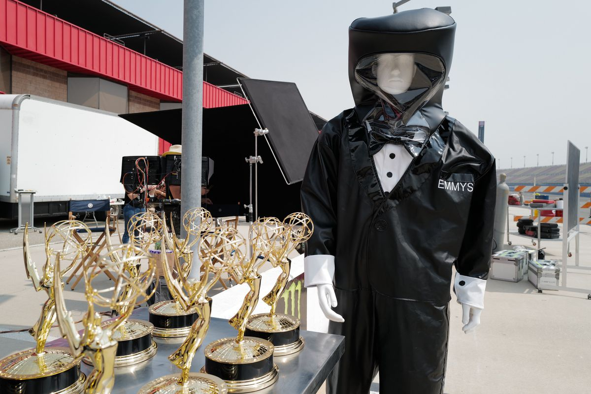 A mannequin in a hazmat suit stands next to Emmy statues.