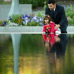 Edgar Farias helps his 1-year-old daughter Cristina look into reflecting pool en route to Hispanic devotional.