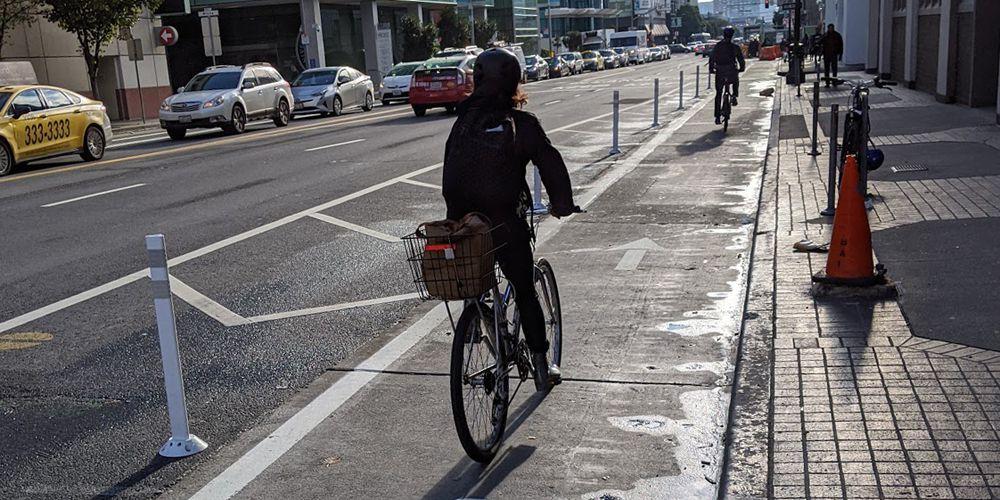 Several people ride bikes down a bike lane beside a street.