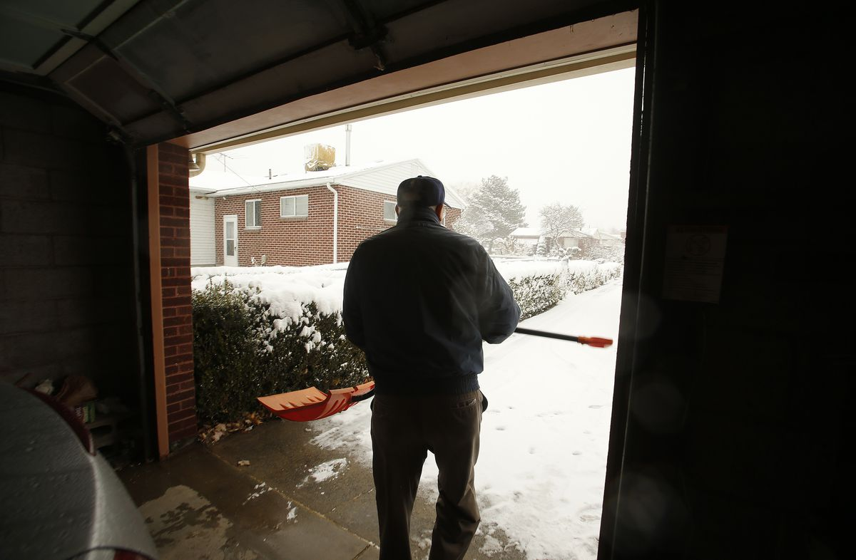 Roger Thompson, 99, gets ready to shovel the sidewalk at his home in Salt Lake City Friday, Dec. 3, 2013.