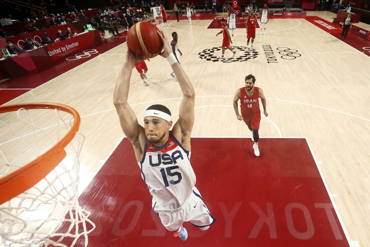 United States' Devin Booker (15) dunks the ball ahead of Iran's Mohammadsamad Nik Khahbahrami (14) during a men's basketball game at the Tokyo Olympics.