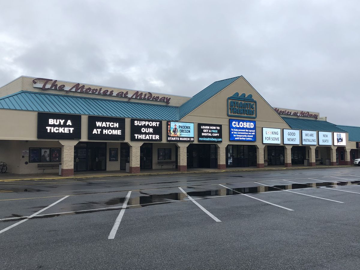 """""""Buy a ticket, watch at home, support our theater"""" are displayed on a movie theater marquee in a strip mall."""