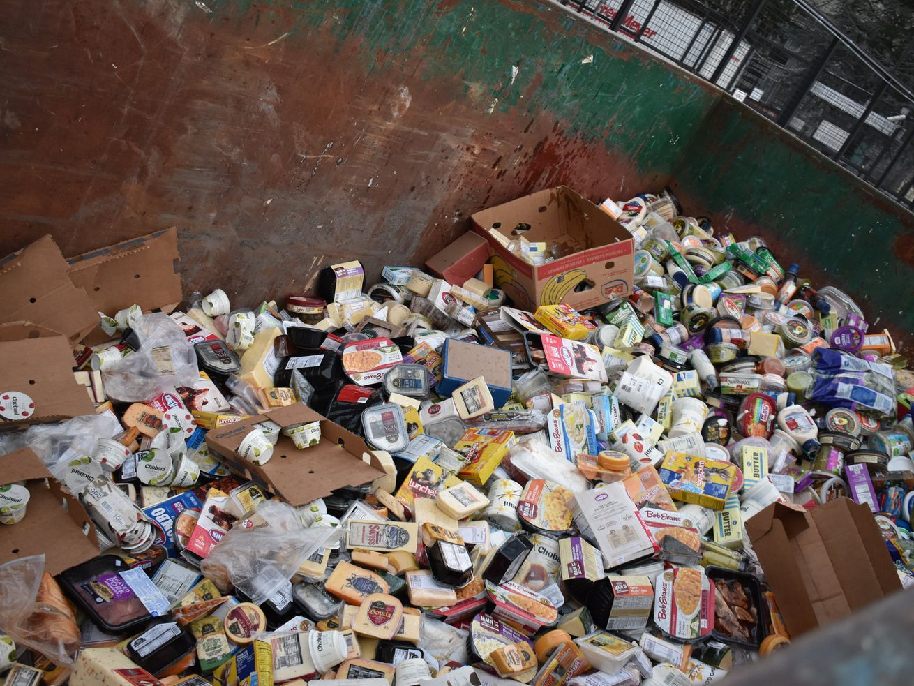 A dumpster filled with cheese and other perishable groceries at Fred Meyer