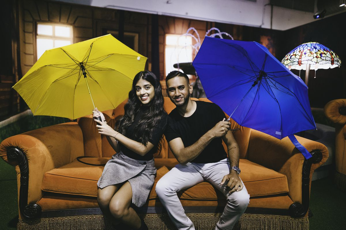 Two individuals pose on an orange couch with yellow and blue umbrellas