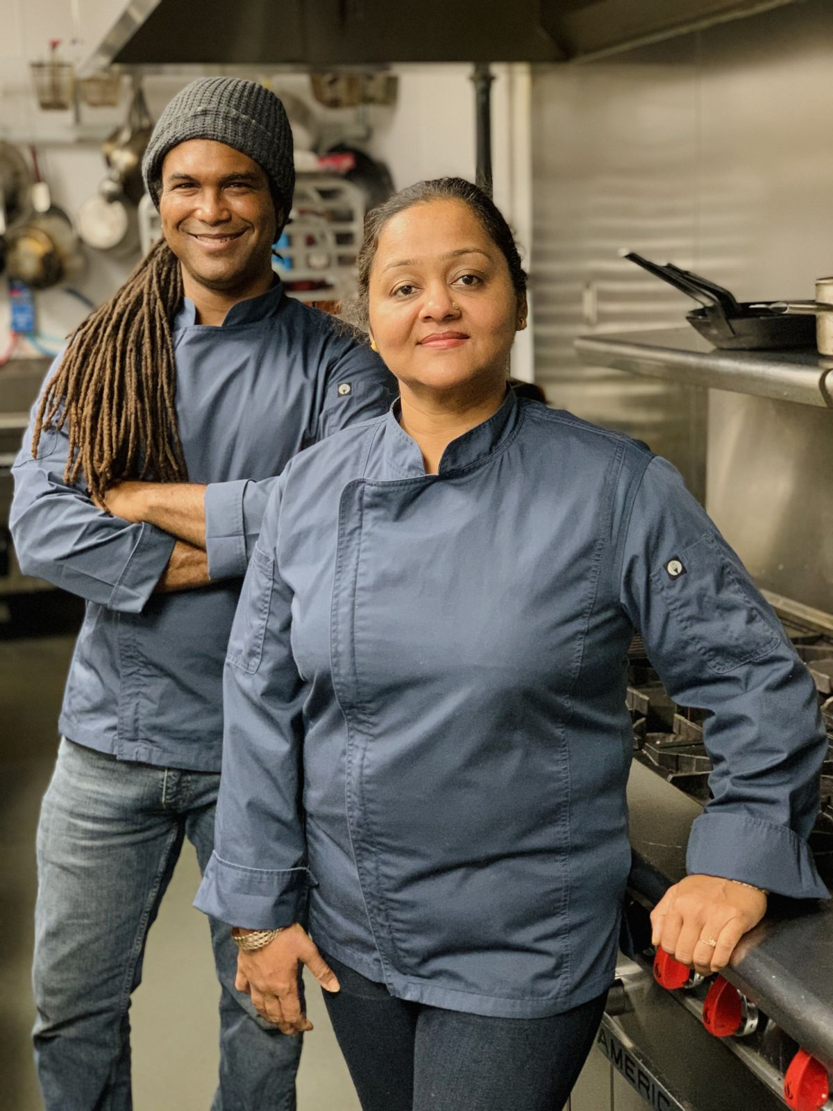 a photo of two chefs in demin blue cooking jackets, standing in a kitchen next to stainless steel appliances. The man, on the lft, has dreadlocks and his arms are crossed at this chest. The woman, on the right, is of Indian descent. She is leaning against the stove.