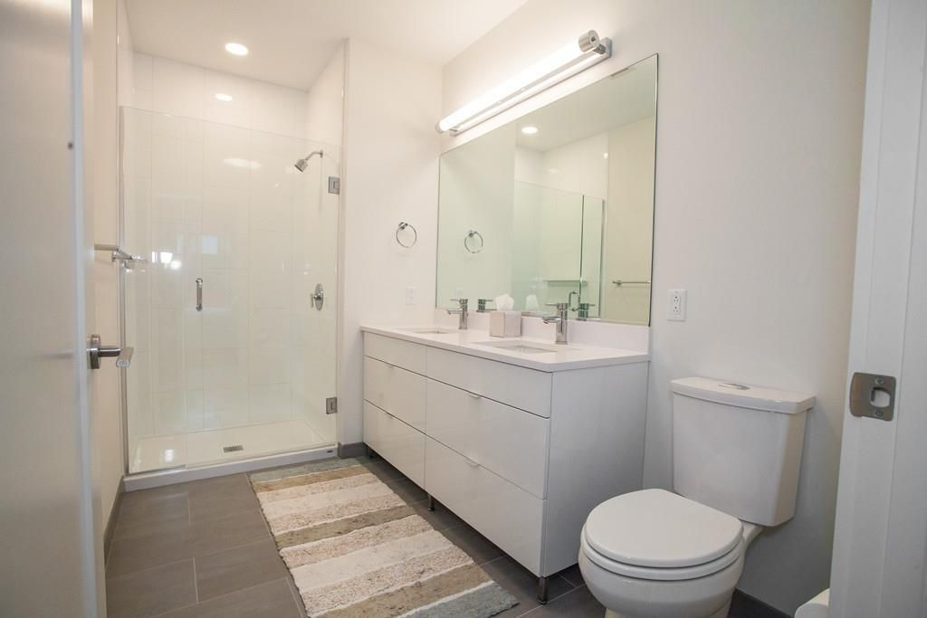 A bathroom with a double-sink vanity and a glass-door shower.