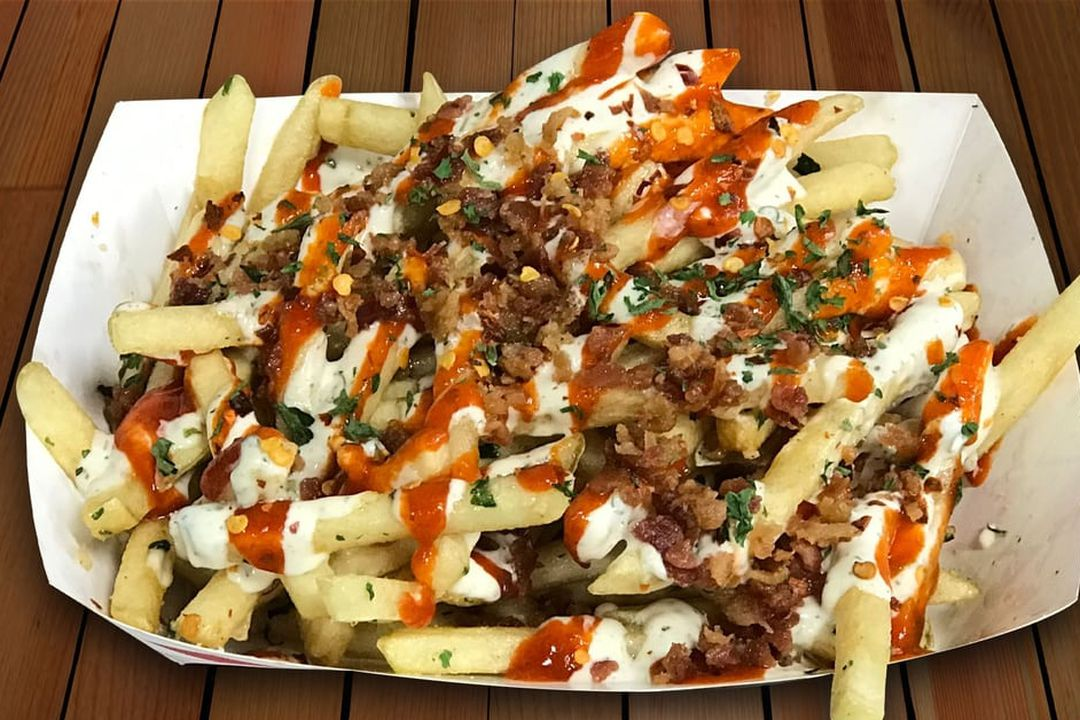 A white paper tray of loaded fries, with sauce and bacon.