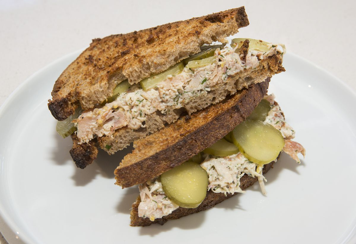 A cross-section of a smoked chicken salad sandwich on toasted bread.