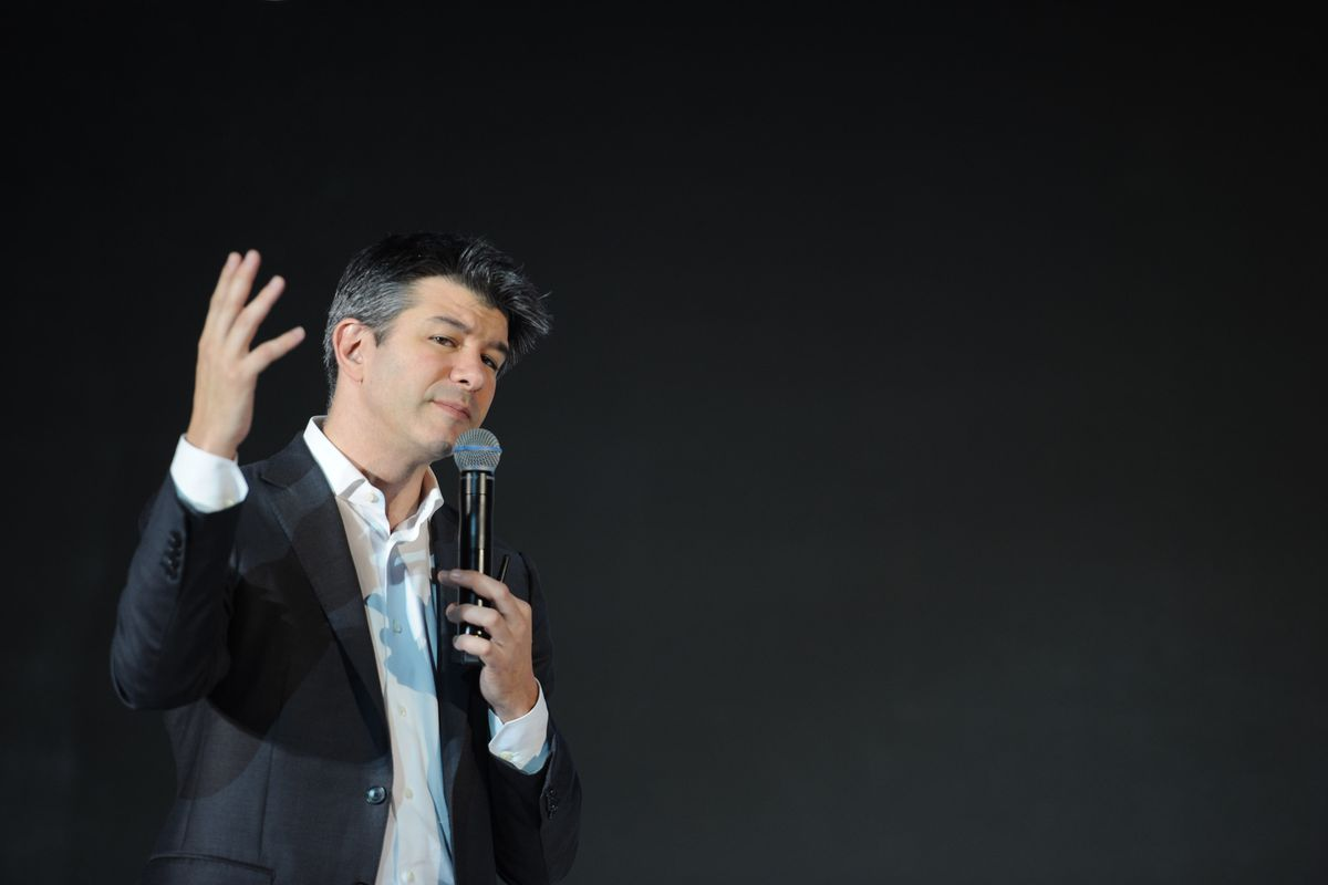 Former Uber CEO Travis Kalanick speaking onstage with a handheld mic.