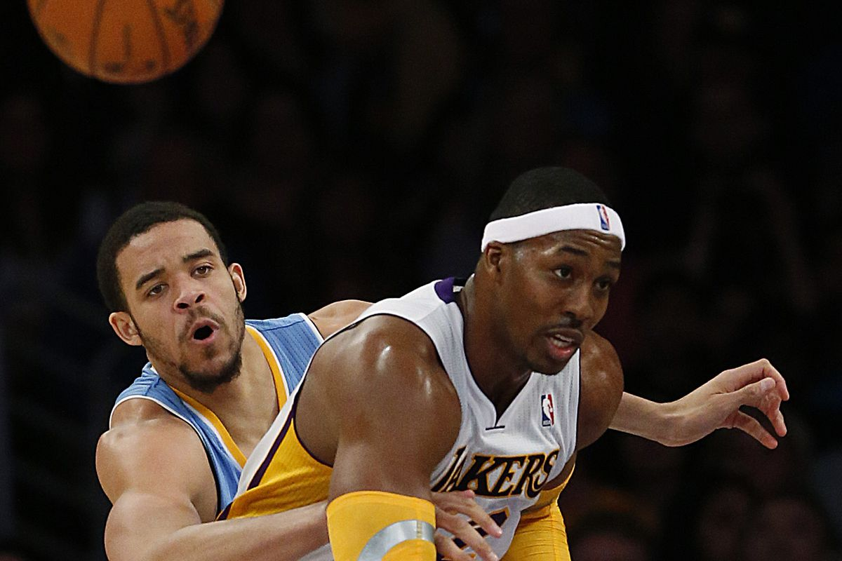 Nuggets defender JaVale McGee knocks the ball from Lakers center Dwight Howard in the second half a