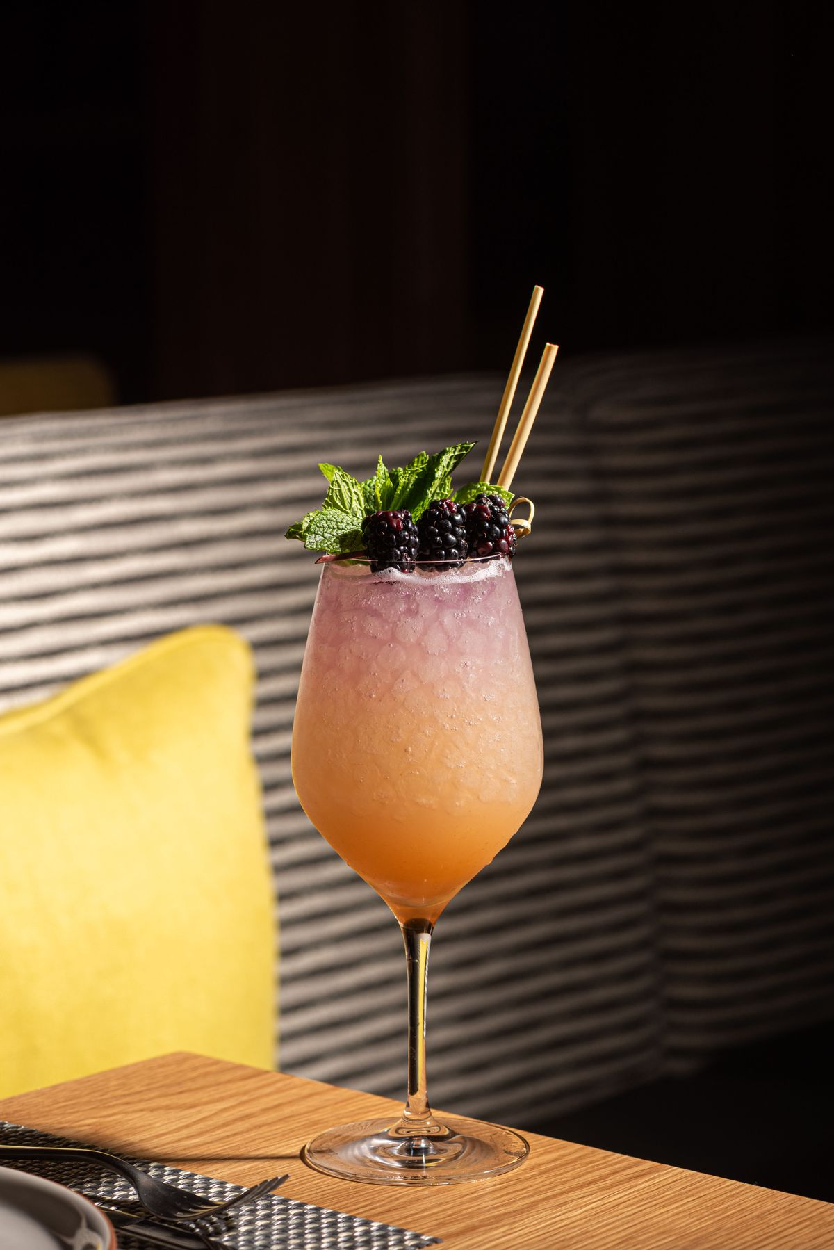 A tall glass of light pink cocktail with crushed ice.