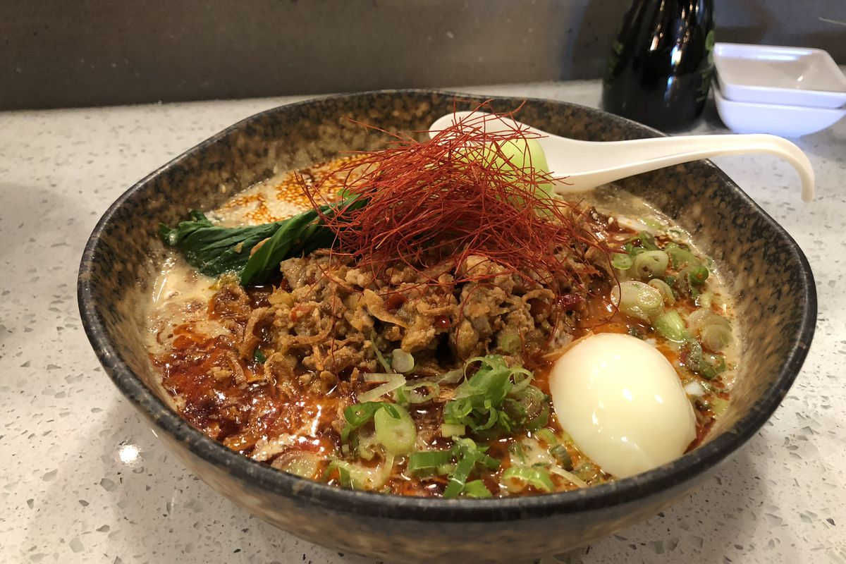 A bowl of ramen containing meat, scallions, a half of a hardboiled egg and other ingredients from Tora Ramen