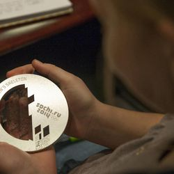"""Becca Linford, 12, holds Noelle Pikus-Pace's olympic silver medal during a small group discussion about Pace's new book, """"Focused: Keeping Your Life on Track, One Choice at a Time,"""" at Deseret Book corporate headquarters, Tuesday, Sept. 9, 2014."""