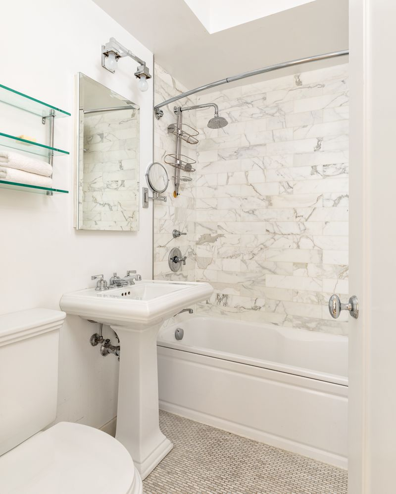 A bathroom with white vein marble.