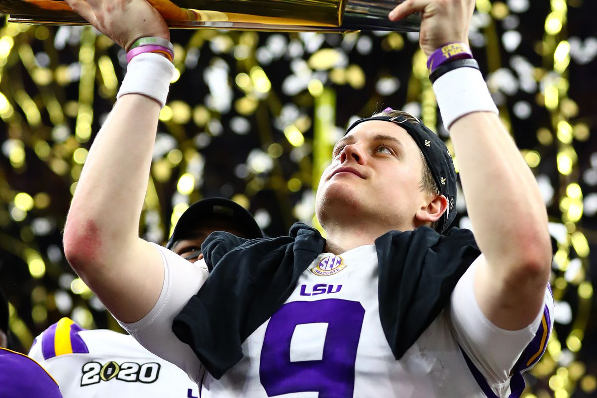 LSU Tigers quarterback Joe Burrow hoists the national championship trophy after a victory against the Clemson Tigers in the College Football Playoff national championship game at Mercedes-Benz Superdome.