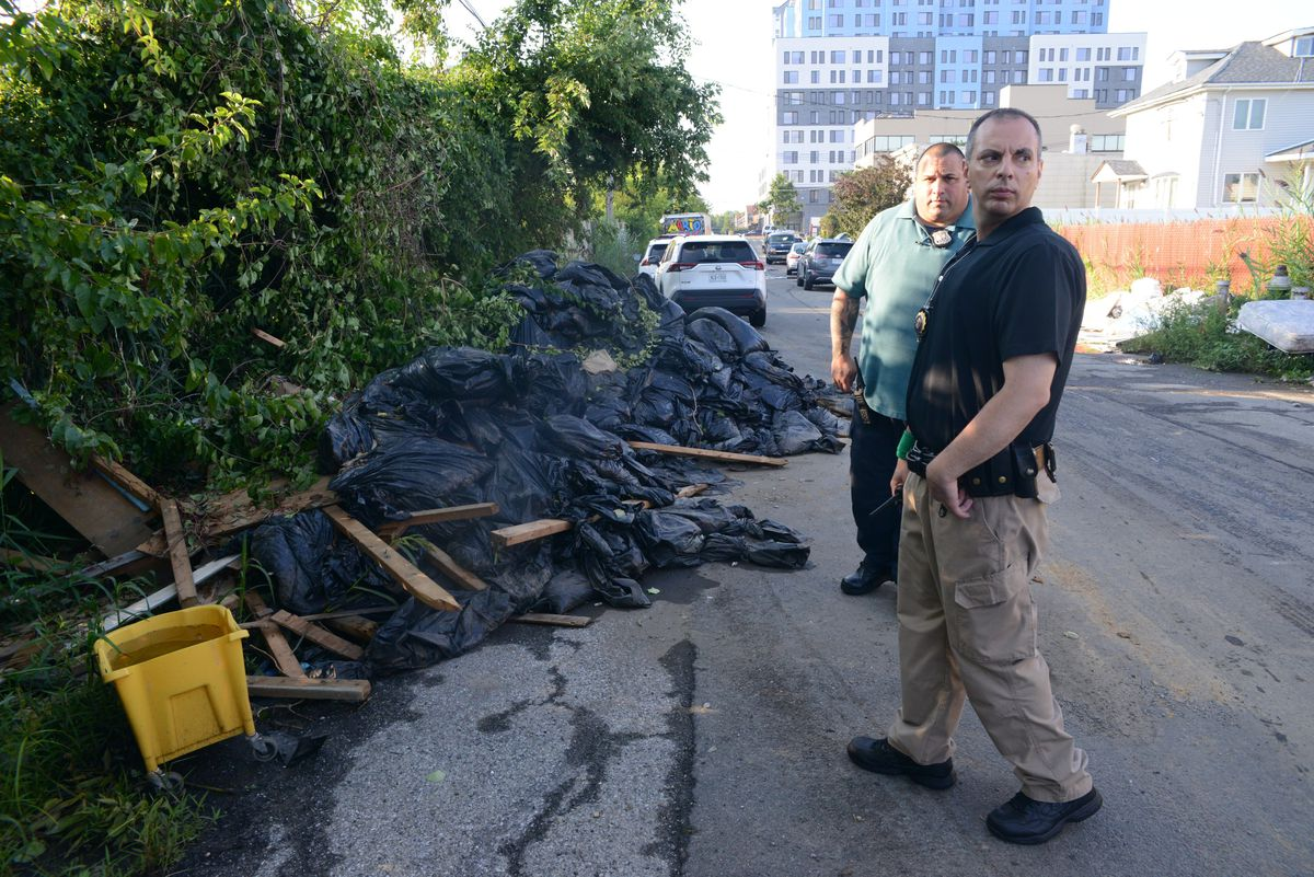 Officer Anthony Rizzo and LieutenantPaul Taranto, who work for the sanitation's police department, observe a large pile of dirt and construction debris in East New York, Brooklyn. The department recently conducted a two-week enforcement blitz in the neighborhood, which has the highest amount of illegal dumping in the city. It's the first in a pilot program that will expand throughout the five boroughs.