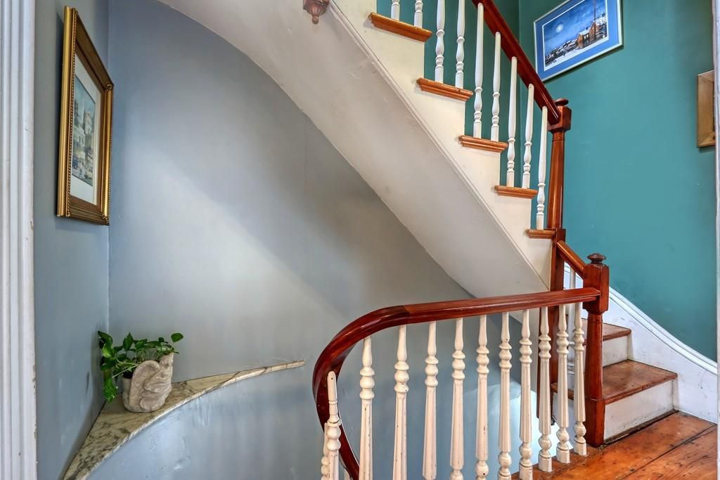 Another landing on the stairs, with the railing featuring prominently and a plant on a little shelf.