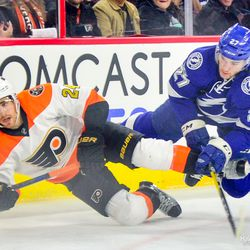 Jonathan Drouin and Matt Read fall to the ice while fighting for the puck in the corner.