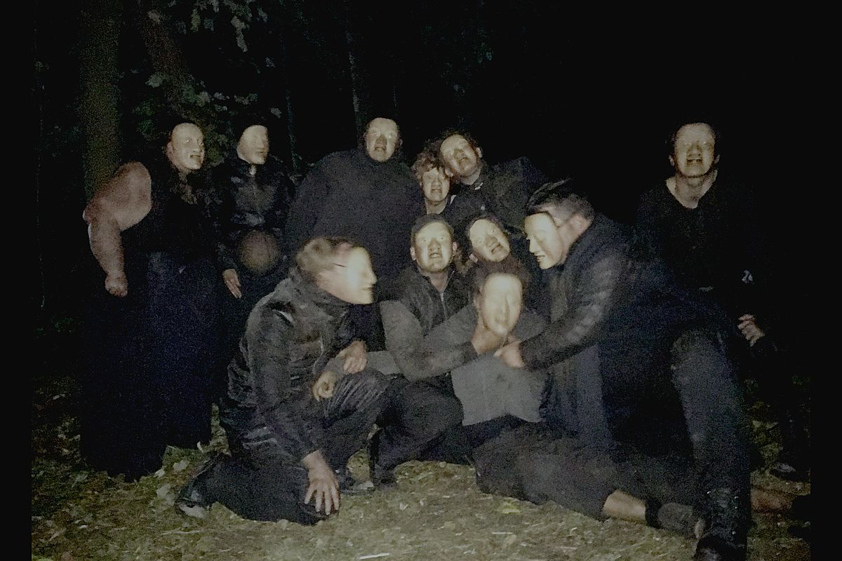 A group of masked people subdue a masked figure at their center.