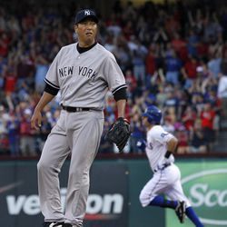 New York Yankees starting pitcher Hiroki Kuroda, of Japan, stands on the mound after giving up a solo home run to Texas Rangers' Ian Kinsler, rear, in the first inning of a baseball game Tuesday, April 24, 2012, in Arlington, Texas.