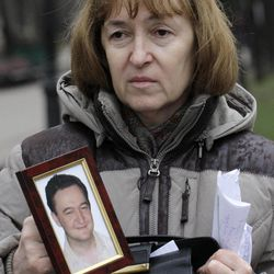FILE - This Monday, Nov. 30, 2009 file photo shows a portrait of lawyer Sergei Magnitsky who died in jail, as it is held  by his mother Nataliya Magnitskaya, as she speaks during an exclusive interview with the AP in Moscow.  Russia's top investigative body says Monday, April 9, 2012, it's dropped charges against a jail doctor in a high-profile prison death case. Sergei Magnitsky was imprisoned for tax evasion in 2008 and died of untreated pancreatitis in Nov. 2009. Magnitsky's death was seen as a litmus case for President Dmitry Medvedev's pledge to cement rule of law in Russia.