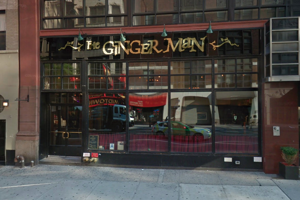 """A red and black restaurant storefront with a large gold sign reading """"The Ginger Man"""""""