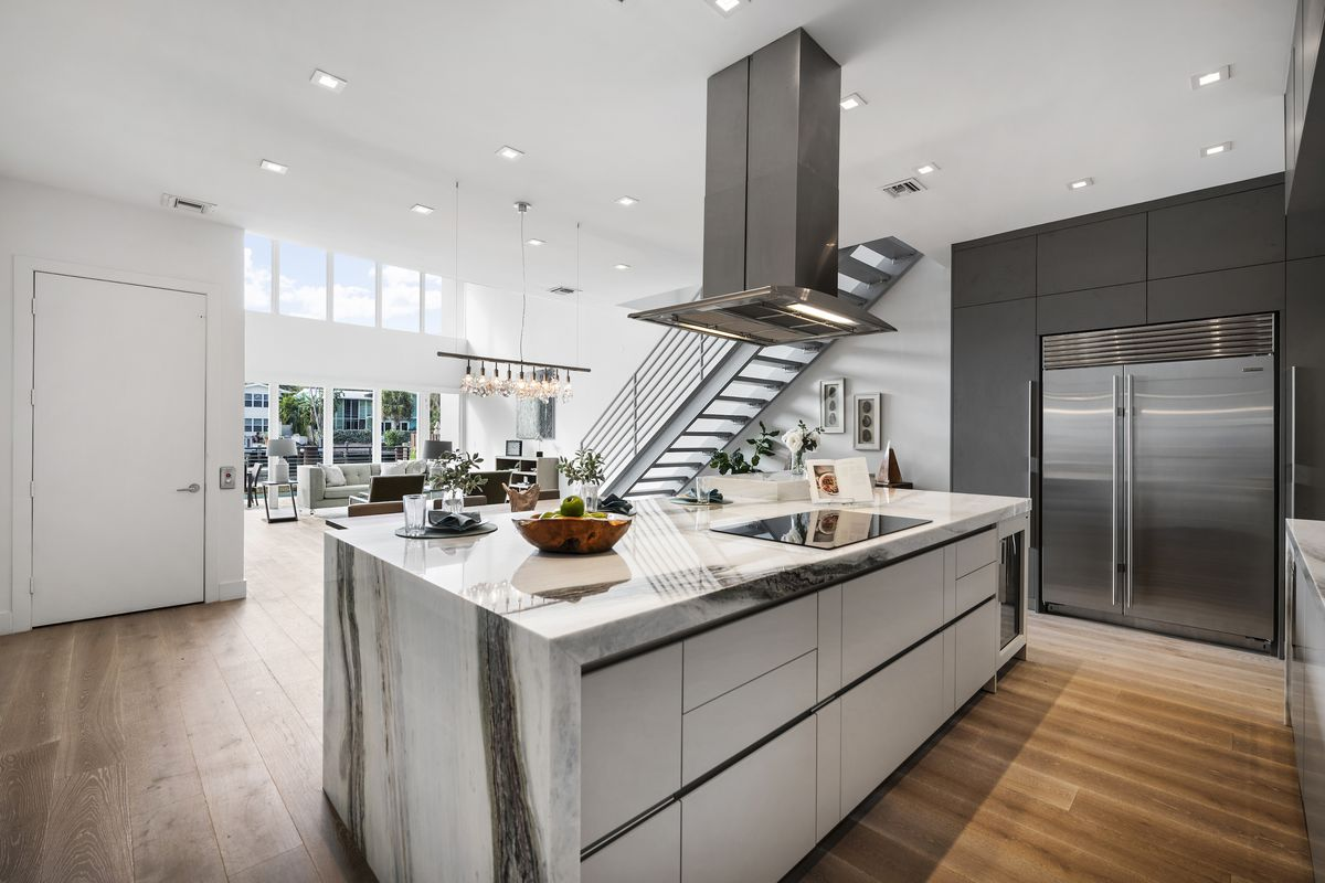 A kitchen has marble counters, white cabinets, and looks out to dining room.