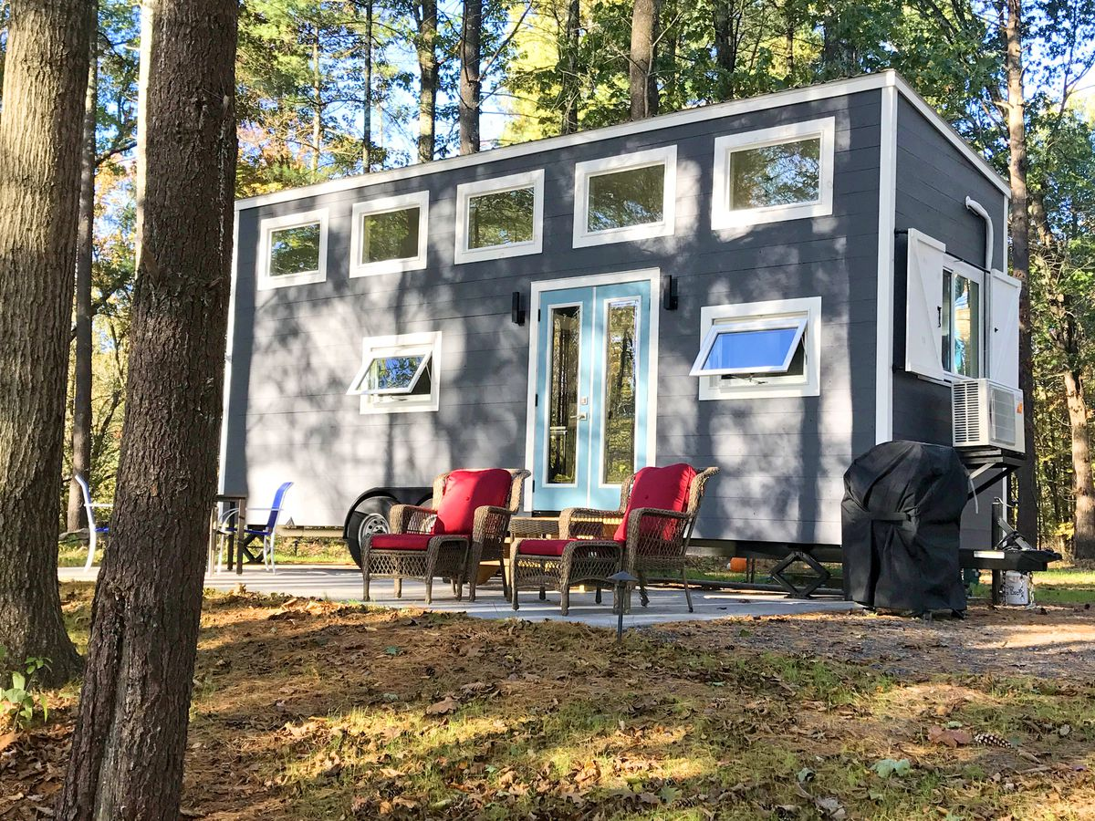 A tiny house with a blue exterior, six windows, and two doors sits in a wooded clearing. Two chairs with red cushions and a grill are situated outside of it.