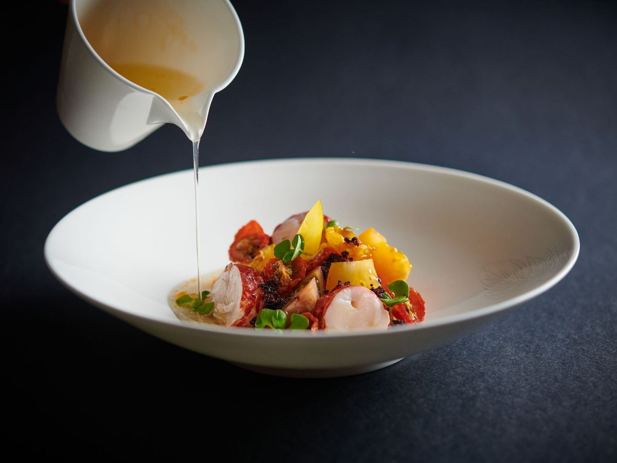 Lobster with tomato, shellfish cream, and olive at The Pem, served in a deep white dish with a jug pouring over broth