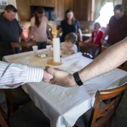 Jeremy Bravo and Matthew Watkin lock hands while praying after receiving communion inside Andy Hogue's home in Leander, Texas, on Sept. 6, 2020.