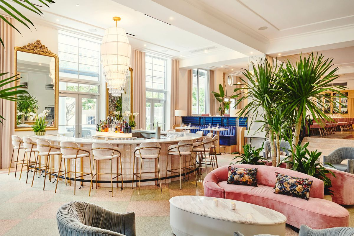 bright bar area with pink dining chairs, wooden tables, Turkish rugs