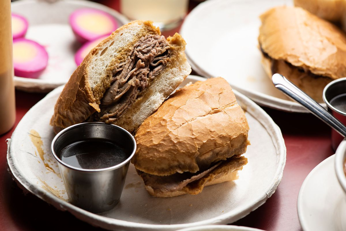 A french dip served on its side with juices in a cup.