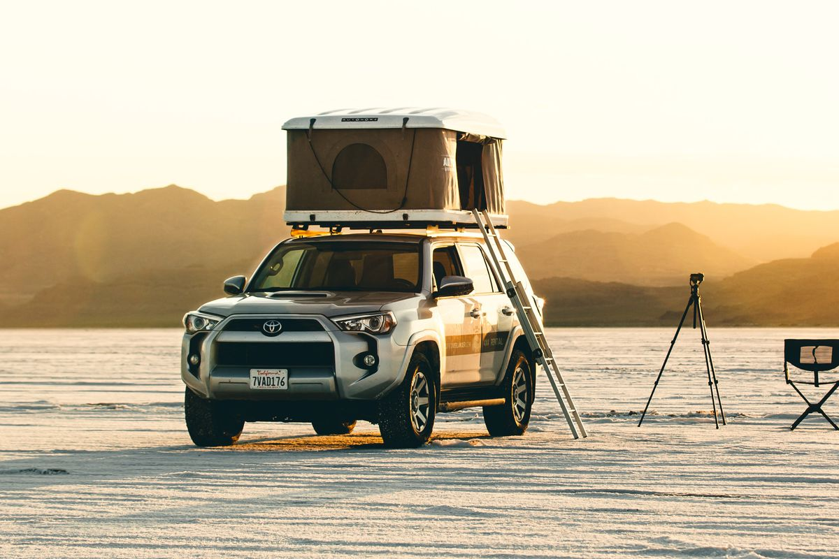 A 4x4 truck is set up to camp in the desert