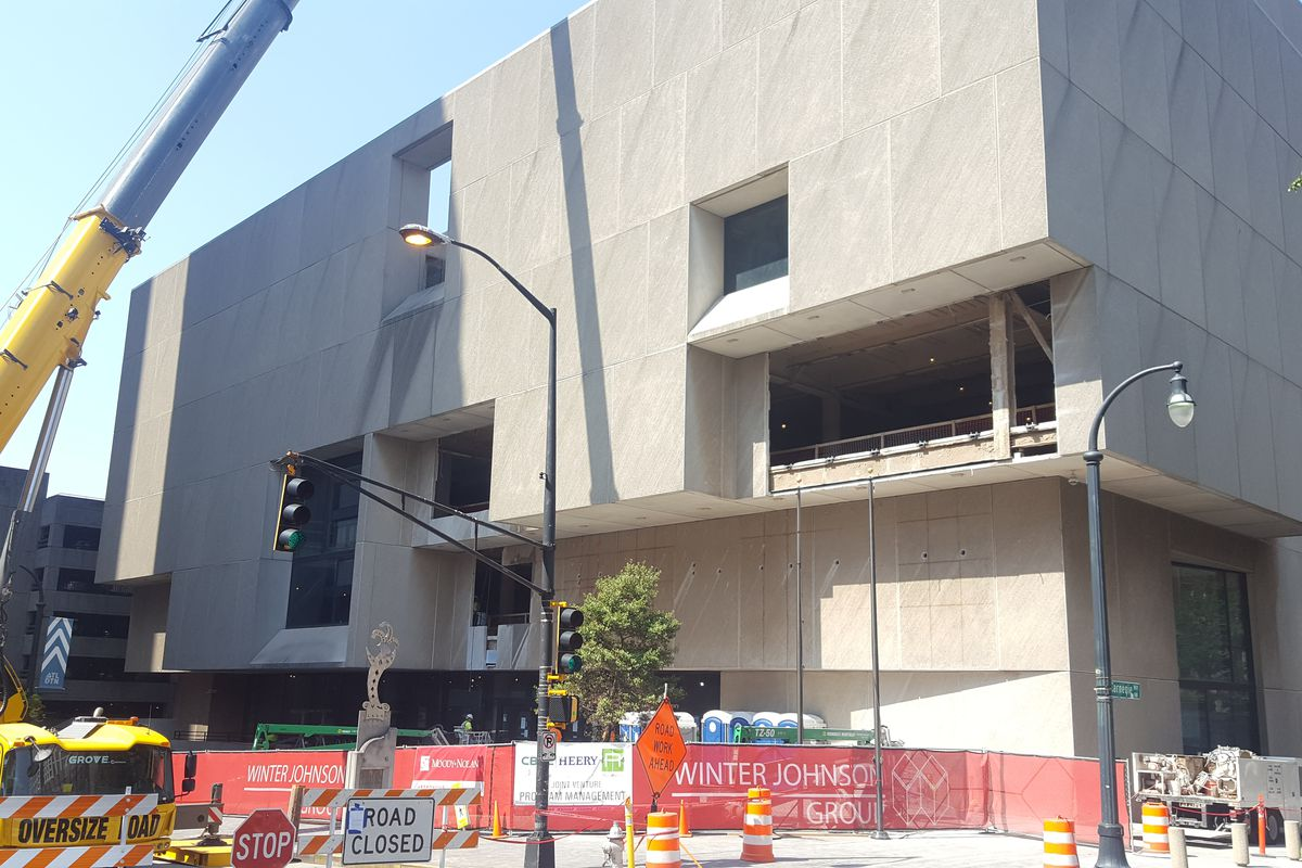Construction crews cut holes into the side of the beefy grey library.