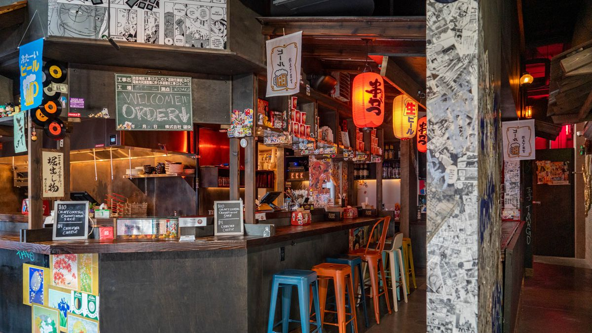 The small counter at Taku on Capitol Hill with paper lanterns and newspaper print and stickers along the walls.