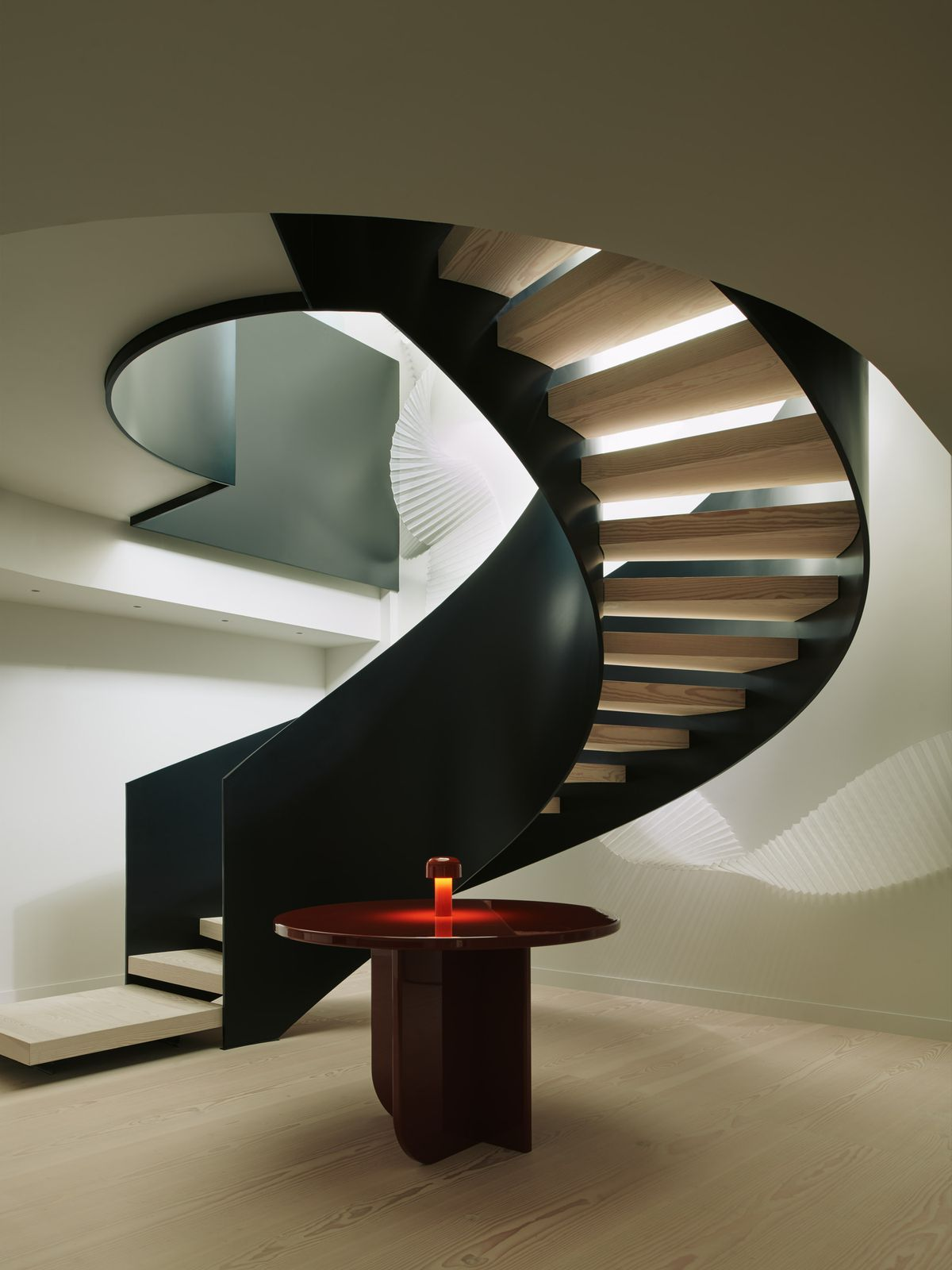 A spiral black staircase and a red round table.