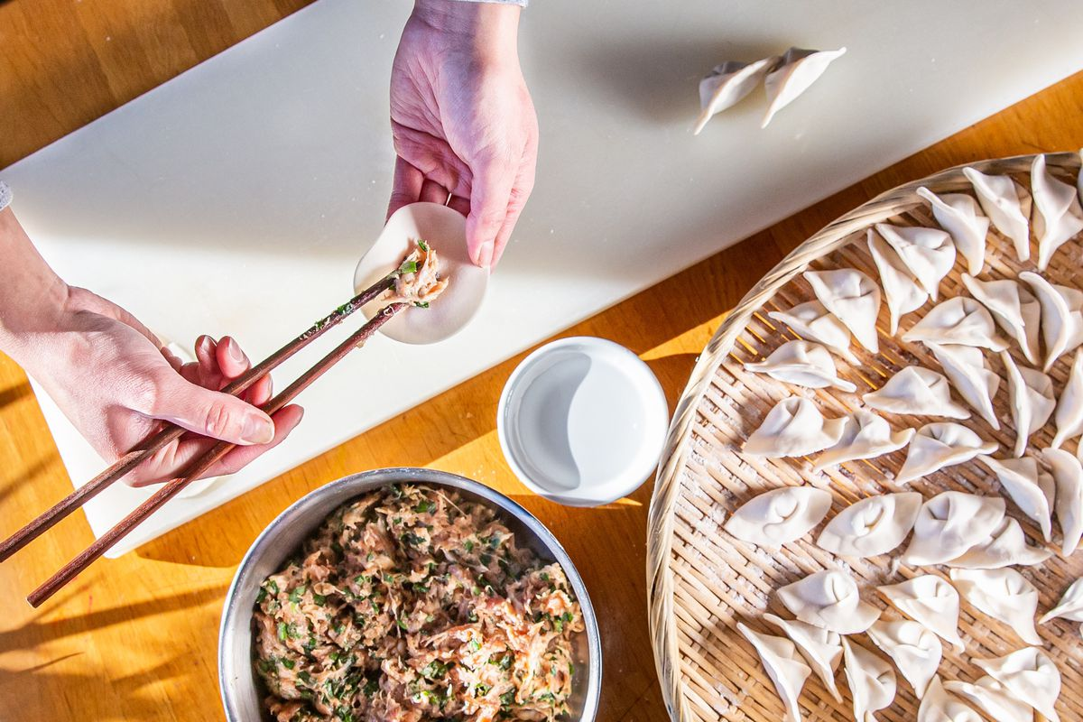 A pair of hands places filling inside a dumpling skin beside a bowl of filling and platter of completed dumplings.