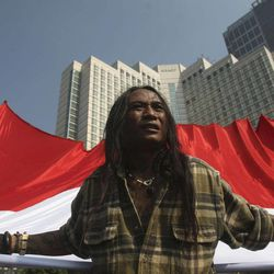 An Indonesian activist holds a huge Indonesian flag during a rally to mark the 10th anniversary of the 9/11 terrorist attacks on the United States, in Jakarta, Indonesia, Sunday, Sept. 11, 2011.