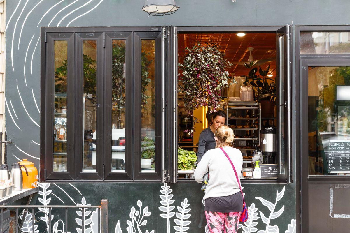 A customer in a white t-shirt stands at a storefront that is painted black with white plants drawn on it