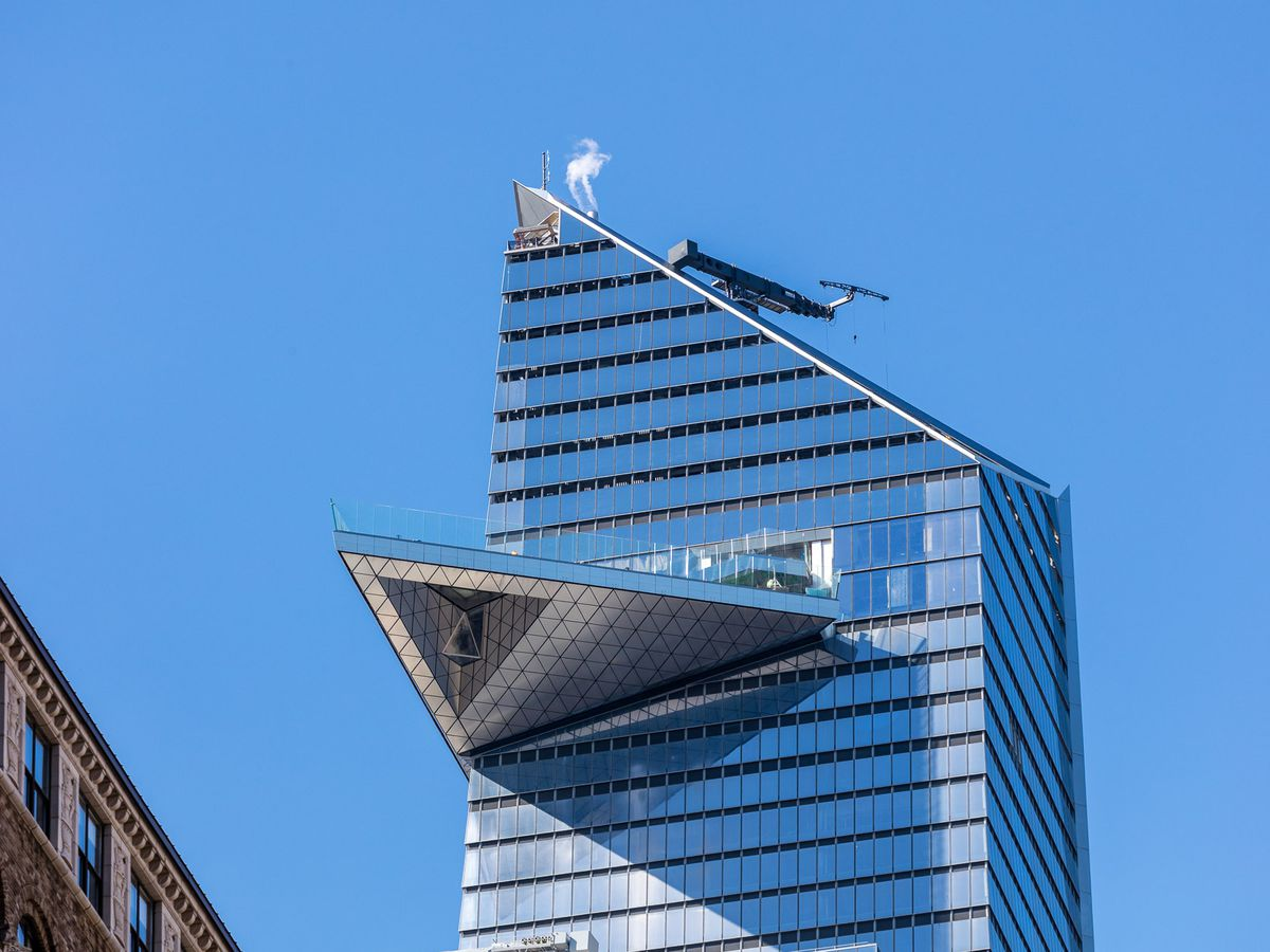 The top of a tall, glass skyscraper, with a large observation deck sticking out from it.