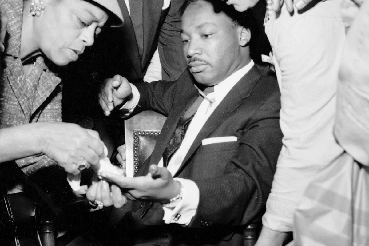 Martin Luther King is treated after an assassination attempt left a letter opener sticking out of his chest.