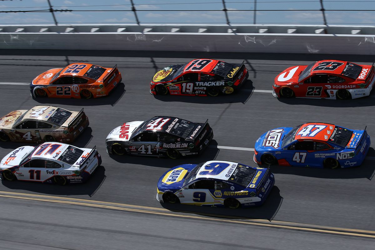 Denny Hamlin, driver of the #11 FedEx Ground Toyota, Kevin Harvick, driver of the #4 Busch Dog Brew Ford, Joey Logano, driver of the #22 Autotrader Ford, Chase Elliott, driver of the #9 NAPA Auto Parts Chevrolet, Cole Custer, driver of the #41 HaasTooling.com Ford, Martin Truex Jr., driver of the #19 Bass Pro Toyota, and Bubba Wallace, driver of the #23 DoorDash Toyota, race during the NASCAR Cup Series GEICO 500 at Talladega Superspeedway on April 25, 2021 in Talladega, Alabama.