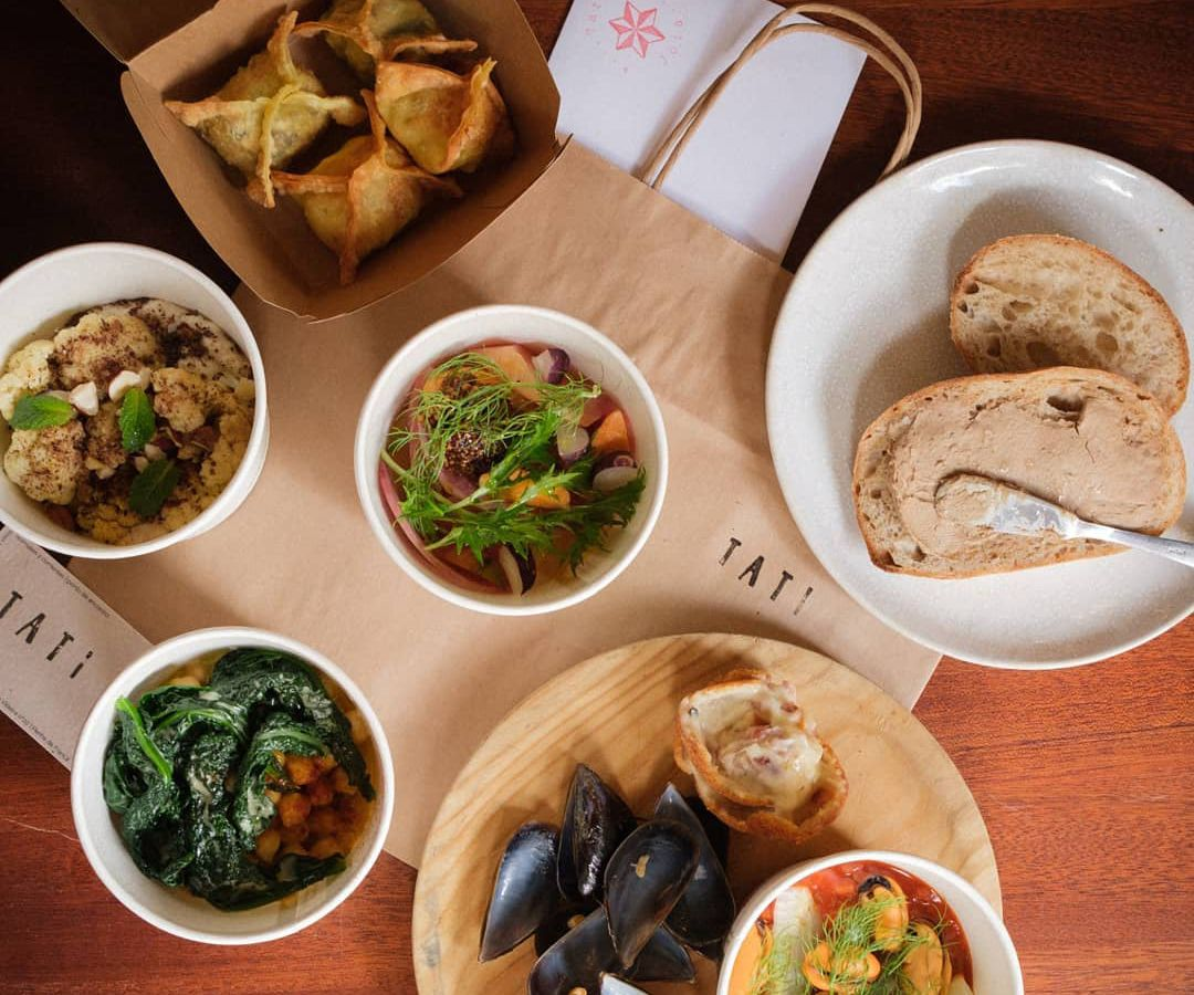 A wood table topped with a variety of dishes and paper bags branded with the Tati name