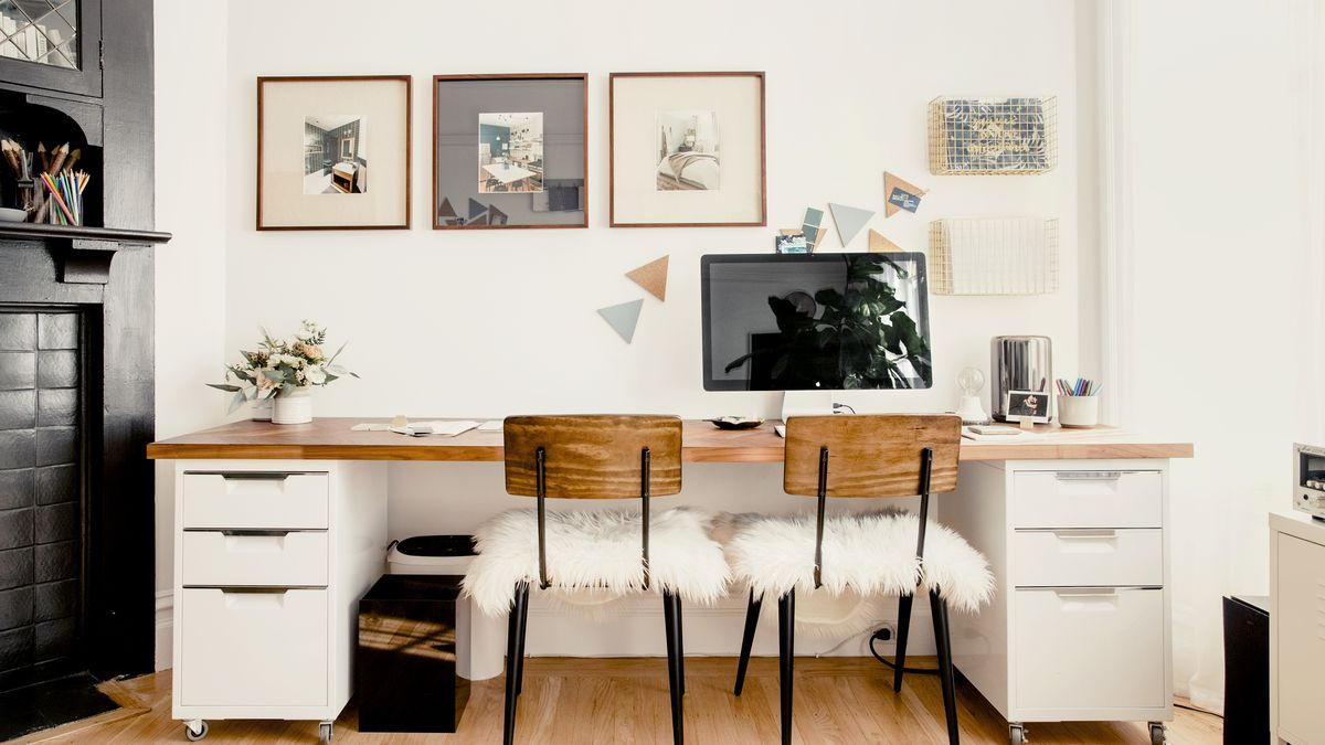An office area. There is a desk with a wood top and white drawers. There are two chairs with fuzzy white cushions. There is a large computer monitor on the desk. Works of art hang over the desk. The walls are white.