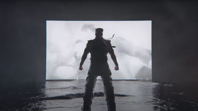 Akira stands in silhouette in front of a screen showing Virtua Fighter footage