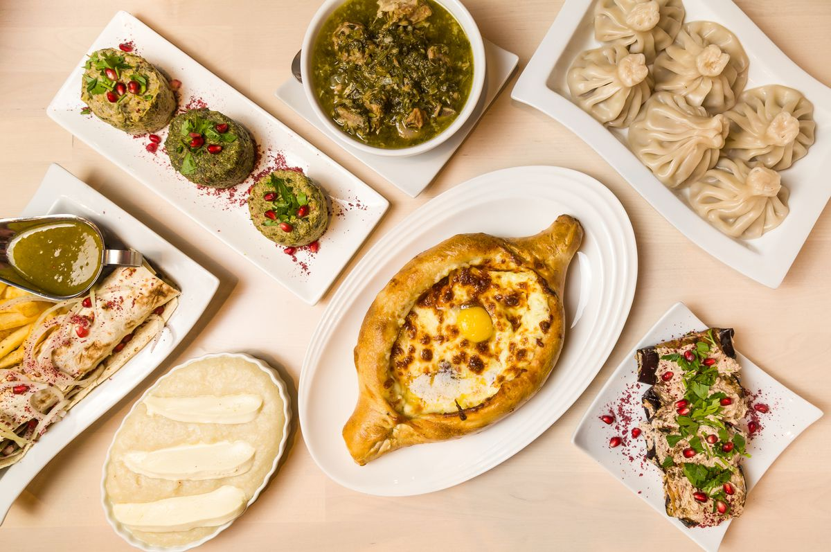 Assorted dishes turn at a 45 degree angle and aligned, including dumplings, composed salads, and meat stews.